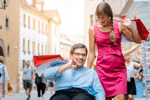 Woman and man in wheelchair with shopping bags