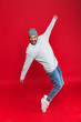 Full length photo of stylish man smiling and jumping isolated over red background
