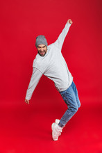 """Постер, картина, фотообои """"Full length photo of stylish man smiling and jumping isolated over red background"""""""
