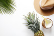 Summer mood concept. Tropical background with ripe organic pinapple with leafy crown, cracked coconut with milk and straw, broad brim hat. Flat lay, top view, copy space, isolated.