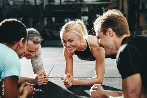 Leinwanddruck Bild Diverse friends smiling while planking together on a gym floor