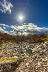 A view of a dry mountain stream with mountain summit in the background under a majestic blue sky, white clouds and shinny sun © Dolwolfian