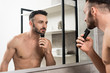 Leinwanddruck Bild - handsome shirtless man holding trimmer while shaving face and looking in mirror in bathroom