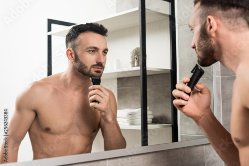 Leinwanddruck Bild handsome shirtless man holding trimmer while shaving face and looking in mirror in bathroom