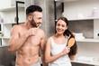 Leinwanddruck Bild - cheerful man looking at attractive girlfriend brushing hair in bathroom