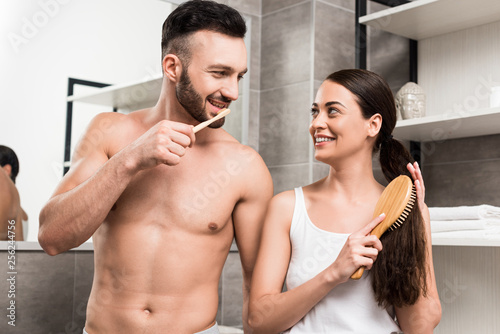 Leinwanddruck Bild handsome shirtless man looking at attractive girlfriend brushing hair in bathroom