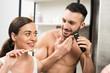 Leinwanddruck Bild - attractive woman holding toothbrush near handsome shirtless boyfriend shaving face in bathroom