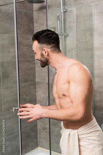Leinwanddruck Bild muscular shirtless man standing near shower cabin in bathroom