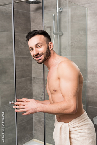 Leinwanddruck Bild muscular bearded man standing near shower cabin in bathroom