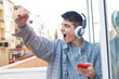 young euphoric with mobile phone and headphones celebrating success
