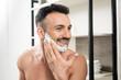 Leinwanddruck Bild - cheerful bearded man applying shaving foam on face in bathroom