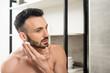 Leinwanddruck Bild - handsome bearded man applying shaving foam on face in bathroom
