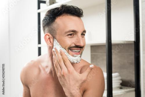 Leinwanddruck Bild cheerful bearded man applying shaving foam on face in bathroom