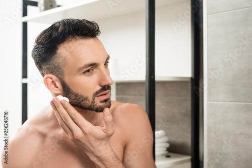 Leinwanddruck Bild handsome bearded man applying shaving foam on face in bathroom