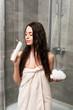 Leinwanddruck Bild - cheerful brunette woman smelling shower gel and holding loofah in bathroom
