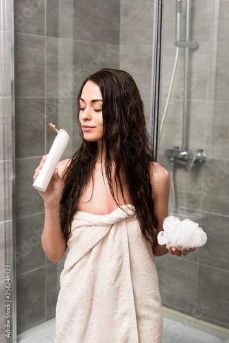 Leinwanddruck Bild cheerful brunette woman smelling shower gel and holding loofah in bathroom