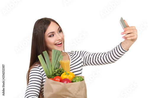 Beautiful woman holding grocery shopping bag and making selfie on smartphone