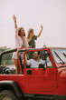 Leinwanddruck Bild - Group of happy young friends having fun in convertible car during summer vacation