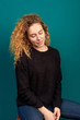 Attractive young curly redhead girl dressed in black sweater and jeans
