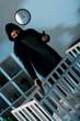 Leinwanddruck Bild - Criminal in mask and hoodie aiming gun at infant child in crib
