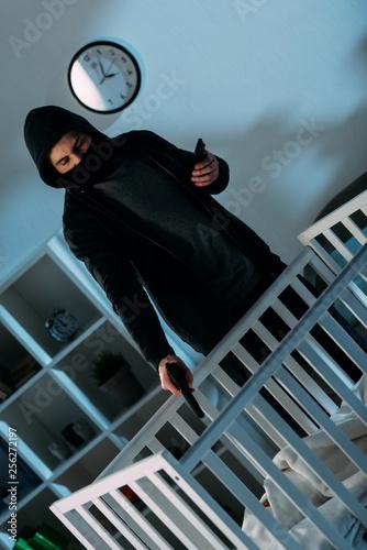 Leinwanddruck Bild Criminal in mask and hoodie aiming gun at infant child in crib