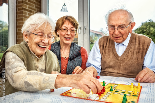Leinwandbild Motiv Elderly couple and daughter playing board game, xxl+more: bartussek.xmstore