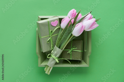 Springtime green paper background with pink tulips, wrapped gift boxes and decorative hearts