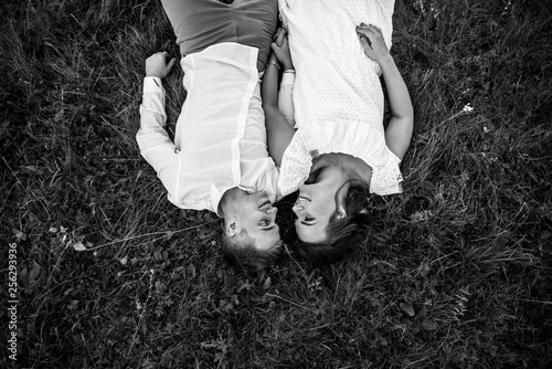 Happy young couple lying on the grass and looking at each other with a smile and love. Top view. Black and white photo