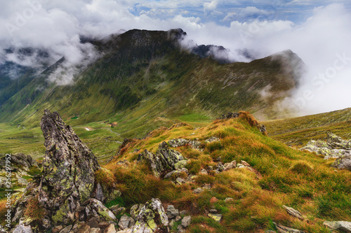 Amazing landscape of summer mountains. View of fog and low clouds over Fagaras Mountains are the highest mountains of the Southern Carpathians. Transylvania. Romania. Travel background.