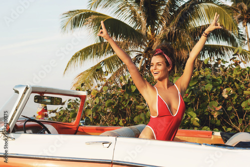 Leinwanddruck Bild Sexy woman in red swimsuit and retro cabriolet car