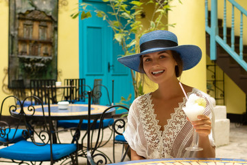 Woman wearing blue hat is enjoying her cold cocktail in city cafe