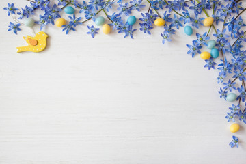 Easter background with blue flowers and candy eggs