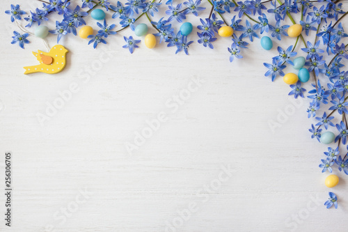 Easter background with blue flowers and candy eggs - 256306705