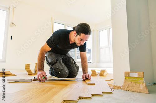Handwerker bei der arbeit, fischgrät parkett verlegen  - 256312945