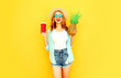 Leinwanddruck Bild - Portrait happy smiling woman holding pineapple, cup of juice having fun in summer straw hat, sunglasses, shorts on colorful yellow background