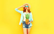 Leinwanddruck Bild - cool girl with pineapple blowing red lips sending sweet air kiss in summer straw hat, sunglasses, shorts on colorful yellow background