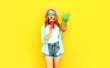 Leinwanddruck Bild - Portrait pretty young woman drinking juice, holding pineapple in summer straw hat, sunglasses, shorts on colorful yellow background
