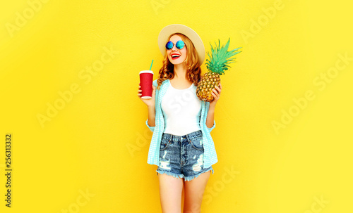 Leinwanddruck Bild Portrait happy laughing woman holding pineapple, cup of juice having fun in summer straw hat, sunglasses, shorts on colorful yellow background