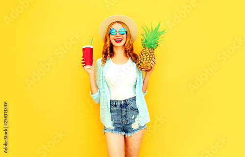 Leinwanddruck Bild Portrait happy smiling woman holding pineapple, cup of juice having fun in summer straw hat, sunglasses, shorts on colorful yellow background