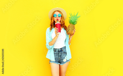 Leinwanddruck Bild Portrait pretty young woman drinking juice, holding pineapple in summer straw hat, sunglasses, shorts on colorful yellow background