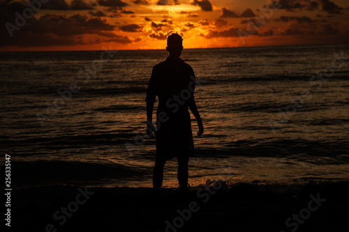 silhouette of man on the beach at sunrise