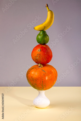 Still life with pumpkins, a vase, bananas and a pear - 256344727