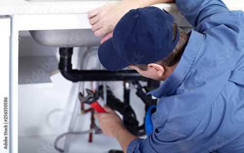 plumber repairs a sink.