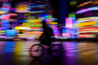 motion blurred of rider ride bicycle with neon light background - 256354559
