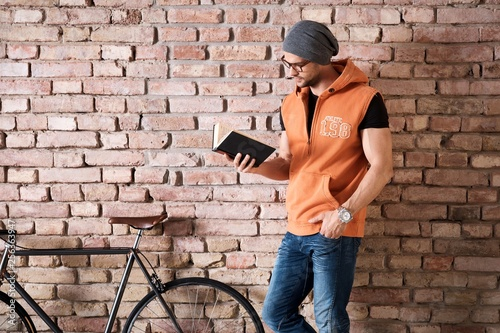 Young man in glasses standing at wall reading book