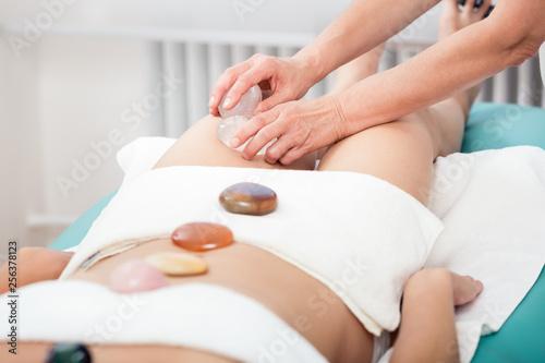 Leinwandbild Motiv Woman receiving thigh massage with stone