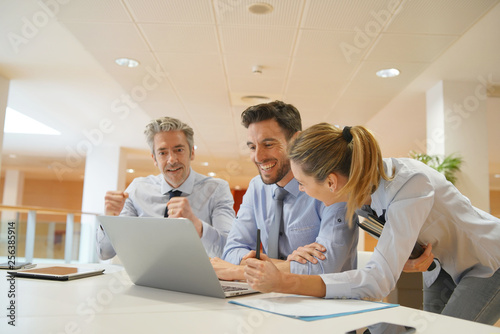 Group of startup coworkers looking at computer in office - 256385914