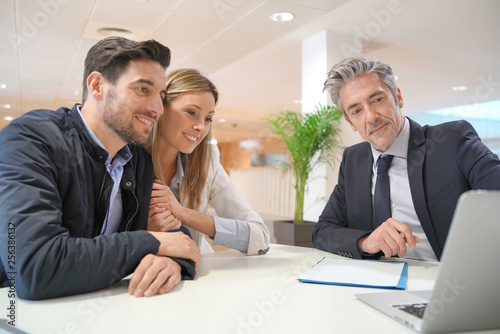 Leinwanddruck Bild Couple signing contract with real estate agent