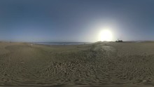 "Постер, картина, фотообои ""GRAN CANARIA, CANARY ISLANDS - AUGUST 02, 2016: 360 VR Video. Scene with people on the ocean coast, Maspalomas Dunes and distant resort against big setting sun, Gran Canaria"""
