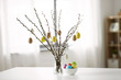 Leinwanddruck Bild - holidays and object concept - pussy willow branches decorated by easter eggs in vase on table
